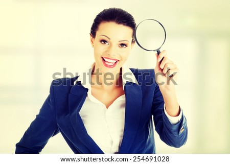 Happy beautiful businesswoman with magnifying glass. - stock photo