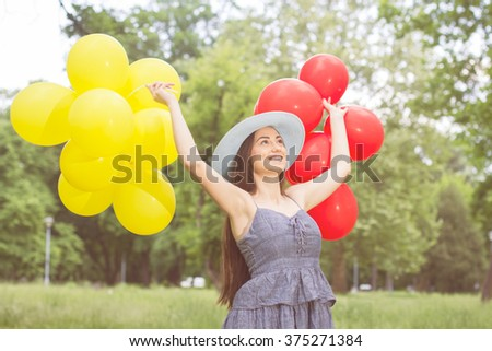 Happy Beautiful Carefree Young Woman with Red and Yellow Balloons. Attractive caucasian female enjoying nature.
