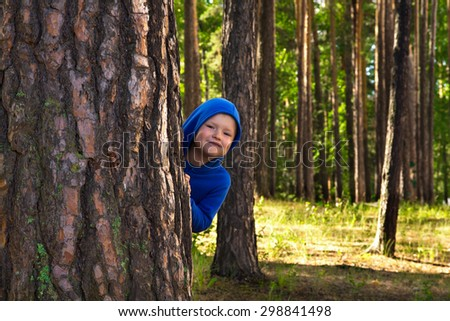 Happy beautiful child (boy) hugging pine, hiding, playing and having fun outdoor in summer forest (park) - stock photo