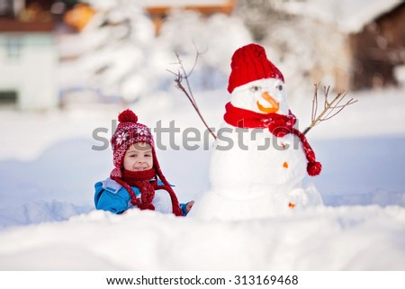 Happy beautiful child building snowman in garden, winter time