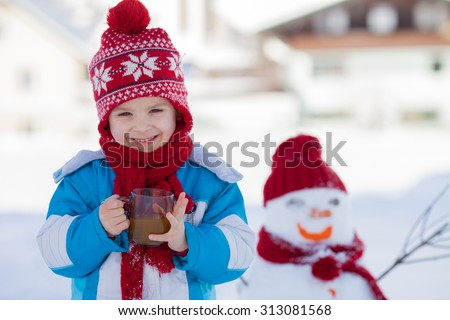 Happy beautiful child building snowman in garden, winter time, holding cup of hot tea, smiling at camera - stock photo