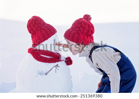 Happy beautiful child building snowman in garden, winter time, nose to nose with the snowman - stock photo