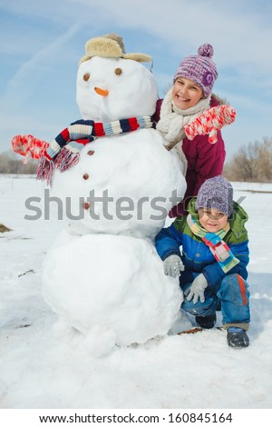 Happy beautiful children with snowman outside in winter time - stock photo