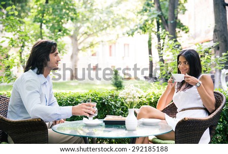 Happy beautiful couple drinking coffee and having romantic time in outdoor cafe - stock photo