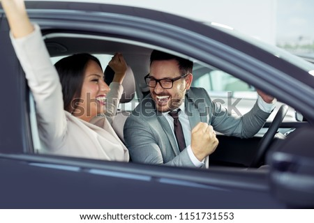 Happy beautiful couple is choosing a new car at dealership