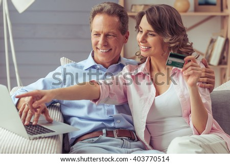 Happy beautiful couple is doing shopping online using a laptop and smiling while sitting on sofa at home