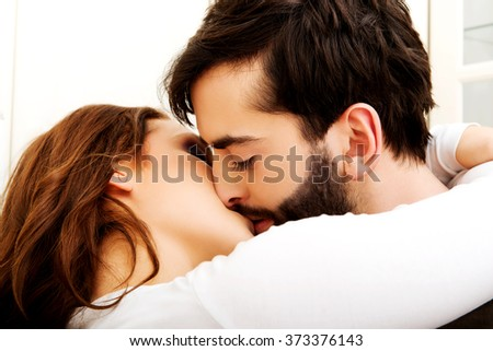 Happy beautiful couple kissing in the kitchen.
