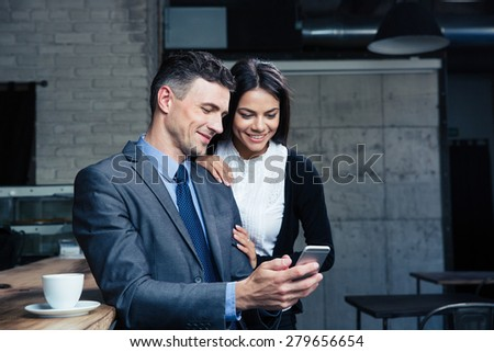 Happy beautiful couple using smartphone in restaurant - stock photo