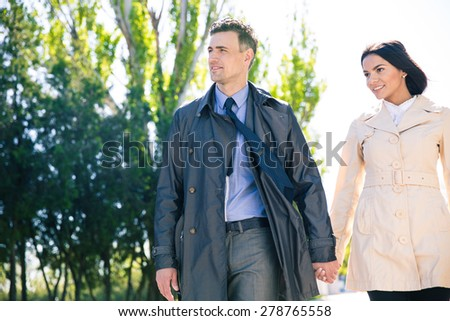 Happy beautiful couple walking outdoors and looking away - stock photo