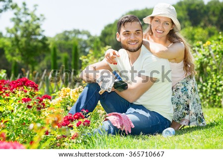 Happy beautiful couple working in the flower garden