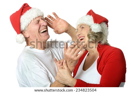 Happy beautiful elderly couple celebrating new year on white background