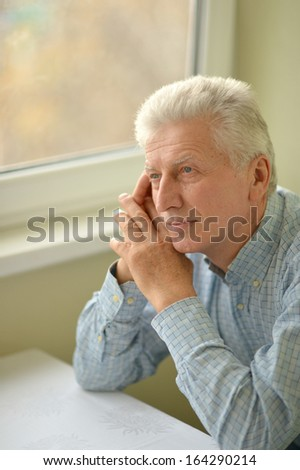 Happy beautiful elderly man relaxing at home