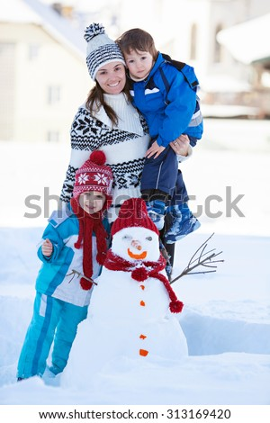 Happy beautiful family building snowman in garden, winter time, mom and two kids - stock photo