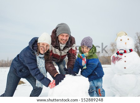 Happy beautiful family building snowman outside in winter time - stock photo