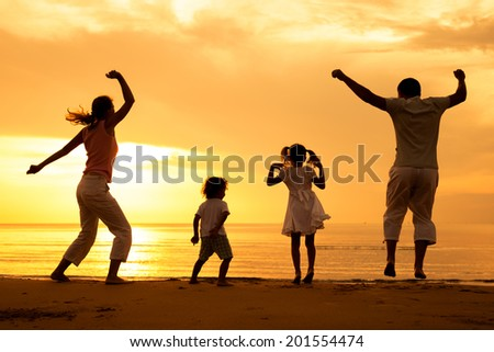Happy beautiful family dancing on the  beach at the  dawn time.