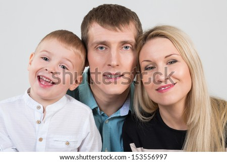 Happy beautiful family of three, son laughs in studio