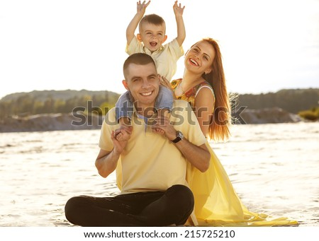 Happy beautiful family on the beach sunset