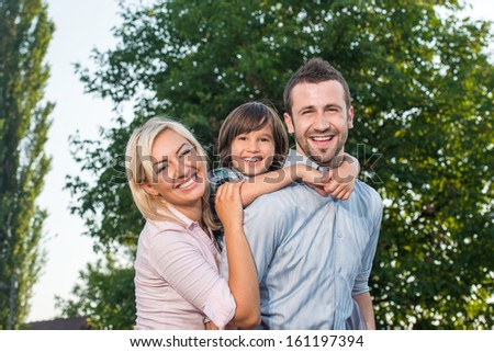Happy beautiful family posing in nature - stock photo