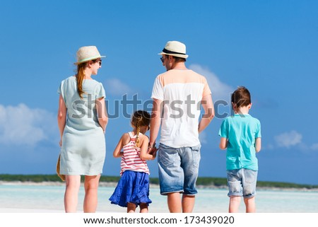 Happy beautiful family walking at beach during summer vacation
