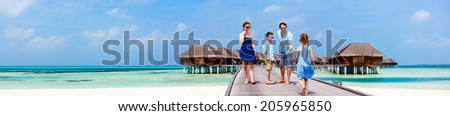 Happy beautiful family walking on wooden jetty during summer vacation at luxury resort wide panorama with copy space, perfect for banners - stock photo