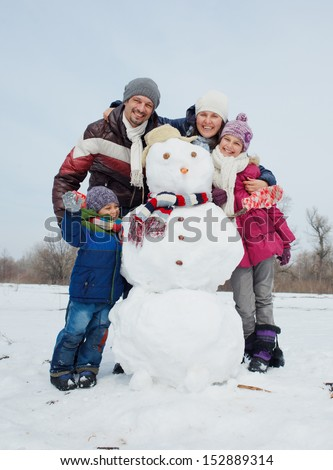 Happy beautiful family with two kids building snowman outside in winter time - stock photo