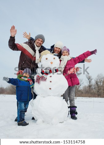 Happy beautiful family with two kids near snowman outside in winter time - stock photo