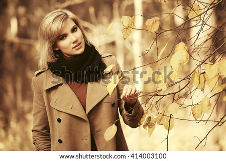 Happy beautiful fashion woman walking in autumn forest. Female stylish model in beige classic coat outdoor - stock photo
