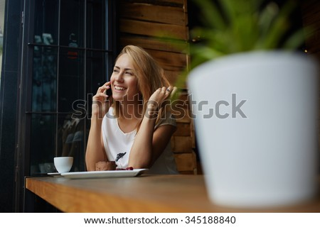 Happy beautiful female with cute smile having cell telephone conversation while sitting in coffee shop during recreation time, smiling woman calling with mobile phone during morning breakfast in cafe  - stock photo
