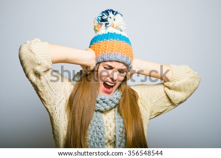 Happy beautiful girl covers his ears with his hands, knitted hat, winter concept, photo studio, portrait of a woman isolated on gray background - stock photo