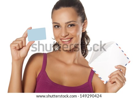 happy beautiful girl holding an envelope and showing her credit card