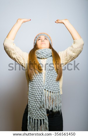 Happy beautiful girl holding something over your head, knit cap, winter concept, photo studio, portrait of a woman isolated on gray background - stock photo