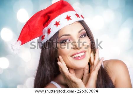 Happy beautiful girl in Christmas hat - stock photo