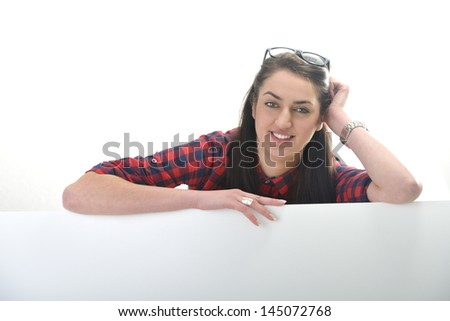 Happy beautiful girl isolated on white leaning on a white cardboard