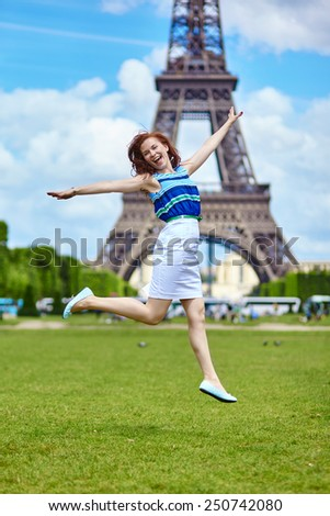 Happy beautiful girl jumping near the Eiffel Tower in Paris - stock photo