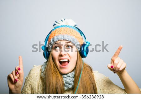 Happy beautiful girl listening to music with big headphones, knit cap, winter concept, photo studio, portrait of a woman isolated on gray background - stock photo