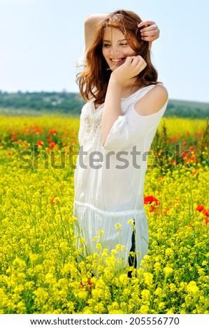 happy beautiful girl on rapeseed field in bloom - stock photo