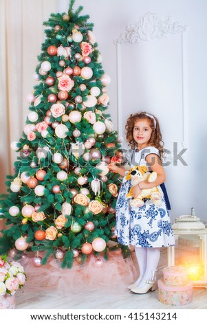 Happy beautiful girl Princess  is hugging  toy on background of the Christmas tree. Happy New Year little Princess - stock photo