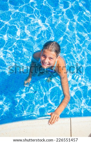 Happy beautiful girl relaxing in the pool. Vertical view