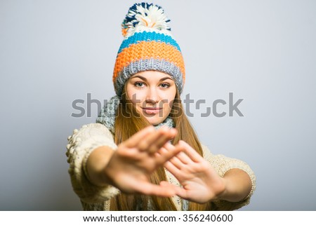 happy beautiful girl showing stop, knit cap, winter concept, photo studio, portrait of a woman isolated on gray background - stock photo