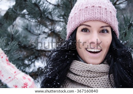 Happy beautiful girl smiling and looking at camera during a snowing day in winter