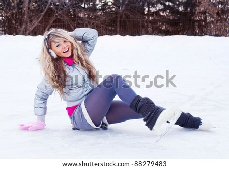 happy beautiful girl wearing warm winter clothes ice skating - stock photo