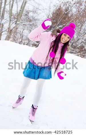 happy beautiful girl wearing warm winter clothes ice skating and playing snowballs - stock photo