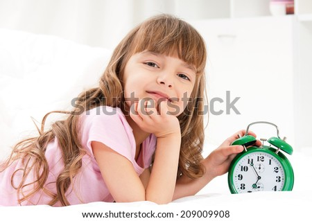 Happy beautiful girl with green alarm clock on bed in the bedroom - stock photo