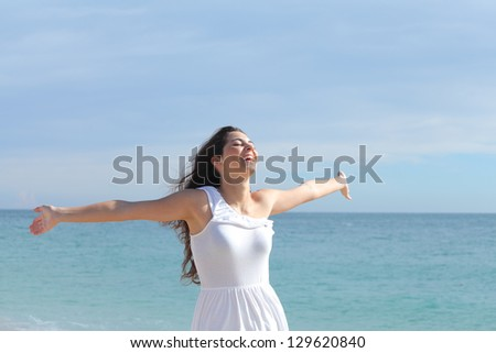 Happy beautiful girl with her arms raised on the beach with the sea in the background