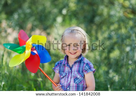 Happy beautiful little blond girl with a large pinwheel or toy windmill in the colours of the rainbow standing outdoors against greenery - stock photo