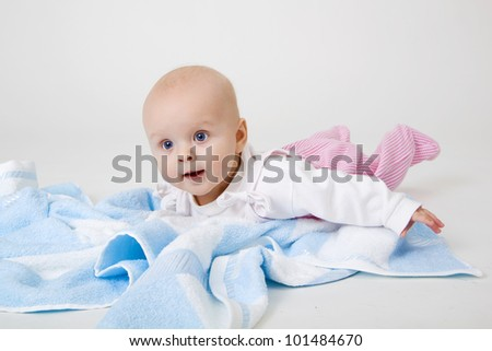 happy beautiful little girl on a blue towel