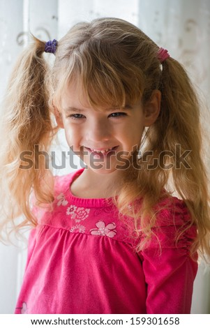happy beautiful little girl posing by the window - stock photo