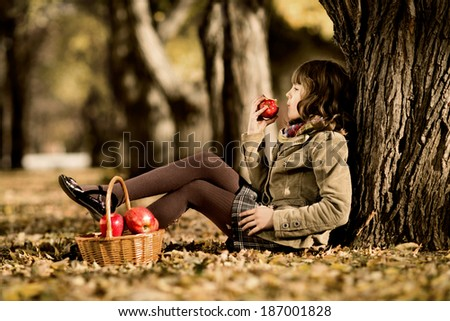 happy beautiful little girl sit on autumnal  leaf and eat apple - stock photo