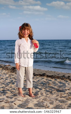 happy beautiful little girl with guitar on beach