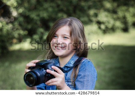 Happy beautiful little girl with photocamera, summer portrait.